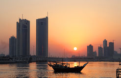 Dhow and Seef skyline during sunset in Bahrain Royalty Free Stock Photo
