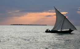 Dhow ship off zanzibar at sunset over prison island royalty free stock photo