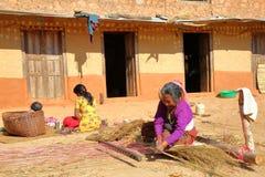 DHULIKHEL, NEPAL - 25 DE DICIEMBRE DE 2014: Mujer mayor nepalesa que hace la cama tejida tradicional usando la paja en el campo c Foto de archivo libre de regalías