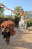 DHULIKHEL, NEPAL - 25 DE DICIEMBRE DE 2014: Mujer mayor nepalesa que lleva la bala pesada de heno en ella detrás en el campo cerc Imágenes de archivo libres de regalías