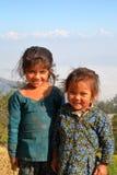 DHULIKHEL NEPAL - DECEMBER 25, 2014: Stående av två gulliga små flickor med de Himalayan bergen i bakgrunden Royaltyfri Fotografi