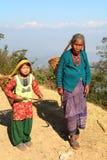 DHULIKHEL, NEPAL - 25. DEZEMBER 2014: Eine alte Frau und ein kleines Mädchen, die in die Landschaft mit einem Korb auf ihrer Rück Stockfoto