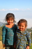 DHULIKHEL, NEPAL - 25. DEZEMBER 2014: Porträt von zwei netten kleinen Mädchen mit den Himalajabergen im Hintergrund Lizenzfreie Stockfotografie