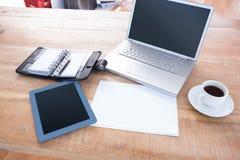 Diário com portátil e tabuleta em uma mesa Imagens de Stock