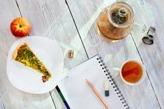Diário, lápis, copo do chá, maçã e relógio na tabela de madeira Imagens de Stock