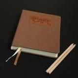 Diário & lápis em um fundo preto Fotografia de Stock