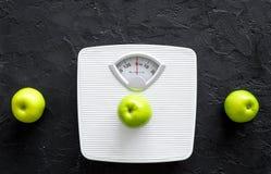 Diät für verlierendes Gewicht Badezimmerwaage und Äpfel auf Draufsicht des schwarzen Hintergrundes Lizenzfreies Stockfoto