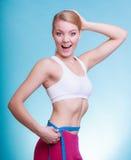 Diät Geeignetes Mädchen der Eignungsfrau mit dem Maßbandmessen ihre Taille Stockfotografie
