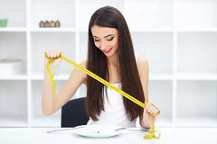 Diät Harte Diät - verbotenes Essen Mädchen hält eine Platte und versucht sich zu setzen lizenzfreies stockfoto