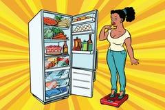 Diät Junge Frau auf Skalen, Stand nahe bei dem Kühlschrank mit stock abbildung