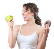 Diät. Junge Frau, die zwischen Frucht und Krapfen wählt lizenzfreie stockfotos