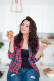 Diät Nährendes Konzept Gesunde Nahrung Schöne junge Frau, die zwischen Früchten und Bonbons wählt Gewichtverlust Frauentorso mit  Stockbilder