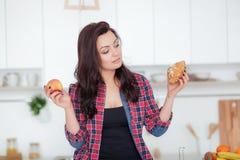 Diät Nährendes Konzept Gesunde Nahrung Schöne junge Frau, die zwischen Früchten und Bonbons wählt Gewichtverlust Frauentorso mit  Lizenzfreie Stockfotografie
