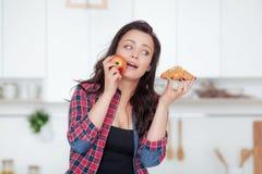Diät Nährendes Konzept Gesunde Nahrung Schöne junge Frau, die zwischen Früchten und Bonbons wählt Gewichtverlust Frauentorso mit  Lizenzfreie Stockfotos