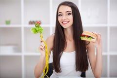 Diät Nährendes Konzept Mädchenwählen gesund gegen ungesunde Fertigkost lizenzfreies stockbild