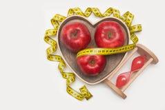 Diät und gesunde Nahrung Glasuhr und rotes reifes Apple im Herzen formen Holzkiste Cyan-blaues messendes Band, lokalisiert auf we Lizenzfreie Stockfotografie