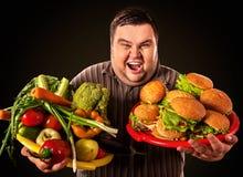 Diätdicker mann trifft Wahl zwischen gesundem und ungesundem Lebensmittel Stockfotos