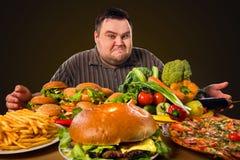 Diätdicker mann trifft Wahl zwischen gesundem und ungesundem Lebensmittel Stockbild