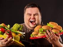 Diätdicker mann trifft Wahl zwischen gesundem und ungesundem Lebensmittel Lizenzfreie Stockfotografie