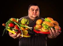 Diätdicker mann trifft Wahl zwischen gesundem und ungesundem Lebensmittel Stockfoto