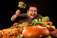 Diätdicker mann trifft Wahl zwischen gesundem und ungesundem Lebensmittel Lizenzfreies Stockbild