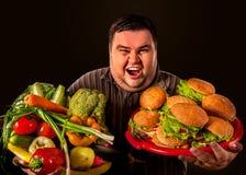 Diätdicker mann trifft Wahl zwischen gesundem und ungesundem Lebensmittel Lizenzfreie Stockfotos