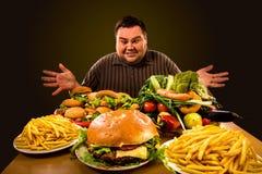 Diätdicker mann trifft Wahl zwischen gesundem und ungesundem Lebensmittel Stockbilder