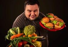 Diätdicker mann trifft Wahl zwischen gesundem und ungesundem Lebensmittel Lizenzfreie Stockbilder