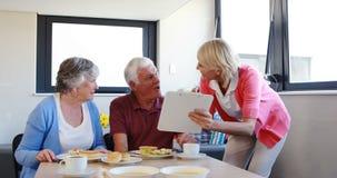 Diätetiker, der Frühstück zu den älteren Paaren unterstützt stock footage