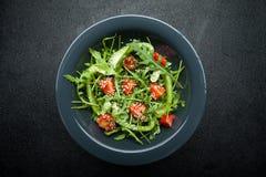 Diätetischer Salat mit Mischkräutern und Gemüse in einer Schüssel auf einem schwarzen Hintergrund lizenzfreie stockfotos