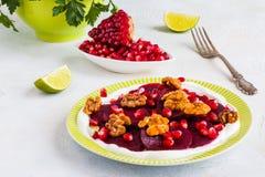 Diätetischer vegetarischer Salat von gebratenen roten Rüben mit Granatapfelsamen, Walnüsse caramelized im Honig und im natürliche Lizenzfreie Stockfotografie
