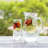 Diätetisches Detoxgetränk mit Zitronensaft, roter Erdbeere, Gurke und tadellosen Blättern im klaren Wasser mit Eis Lizenzfreies Stockfoto