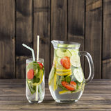 Diätetisches Detoxgetränk mit Zitronensaft, roter Erdbeere, Gurke und tadellosen Blättern im klaren Wasser mit Eis Lizenzfreie Stockbilder