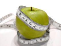 Diätfrucht mit Maßband (grüner Apfel) stockbild