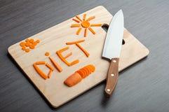 Diätkonzept. Auslegungsnahrung. Wortdiätkarotten auf einem Schneidebrett Stockbild