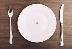 Diätkonzept. eine Erbse auf einer leeren weißen Platte Stockfoto