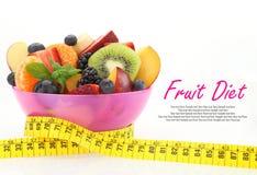 Diätmahlzeit. Obstsalat in einer Schüssel mit messendem Band Stockbilder