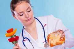 Diététicien avec le petit pain et les légumes de petit pain doux Photographie stock libre de droits