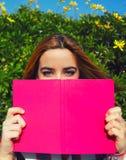 ¡ Di Ð che nuoce alla giovane donna con il libro rosa sostenuto vicino al suo fronte Fotografie Stock