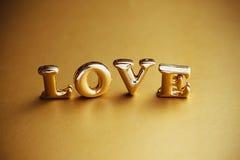 ` Di amore del ` di parola singola nell'iscrizione dell'oro Fotografie Stock