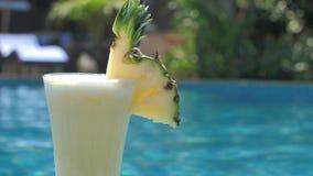 Di ananas succo di recente con la fetta di frutta sul fondo blu dello stagno al giorno soleggiato archivi video
