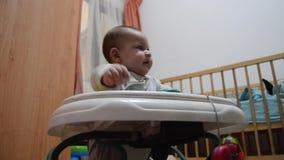 Di angolo basso del neonato del colpo sei mesi svegli nello sviluppo iniziale del camminatore, imparante come camminare stock footage