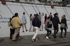 Di camminata di passato della gente imbarcato su costruzione Fotografie Stock Libere da Diritti