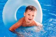Di cinque anni allegro sveglio in un cerchio gonfiabile per il nuoto nello stagno fotografie stock libere da diritti