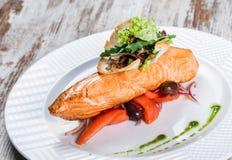 Di color salmone cotto guarnito con le olive, verdi, pomodori sul piatto sopra fondo di legno Piatto di pesci caldo fotografia stock