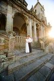 Di divertimento abbraccio della coppia sposata recentemente vicino alla chiesa Fotografie Stock Libere da Diritti