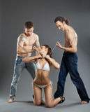 Di due uomini catturi la donna sulla catena - giochi del bdsm Immagini Stock