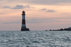 19/09/2018 di Eastbourne, Regno Unito Faro capo sassoso nel mare ed il tramonto sui precedenti fotografia stock