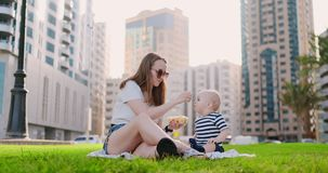 di estate in parco la mamma alimenta il bambino dal pranzo del contenitore video d archivio