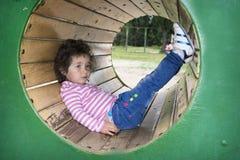di estate sul campo da giuoco la bambina si trova in un tunnel Immagini Stock Libere da Diritti